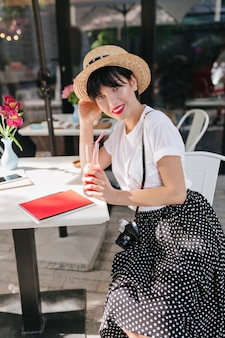 Elegante garota de cabelo preto com camisa branca e saia de bolinhas descansando em um café com um copo de coquetel gelado após a sessão de fotos
