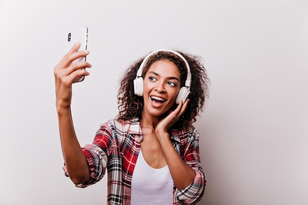 Elegante garota negra ouvindo música enquanto tira uma foto de si mesma. mulher entusiasmada usando telefone para selfie.