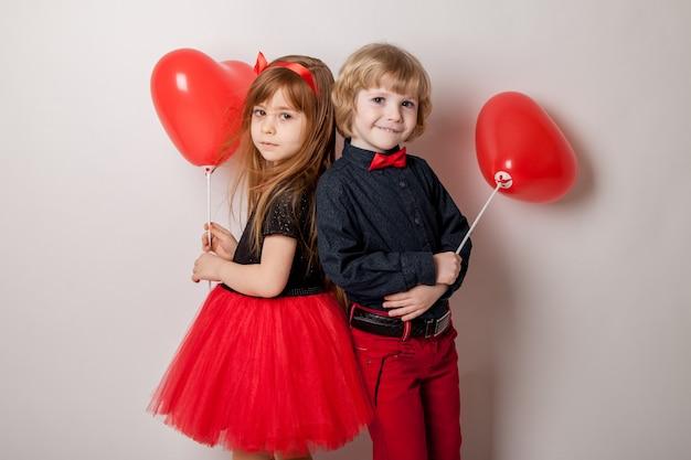 Elegante garotinho segurando balões em forma de coração e sorrindo linda garotinha isolada no branco