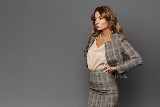 Elegante gerente do ceo feminino de terno xadrez, olhando para o lado e posando em um fundo cinza, isolado. bela jovem empresária em fundo cinza com espaço de cópia à esquerda. advogada.