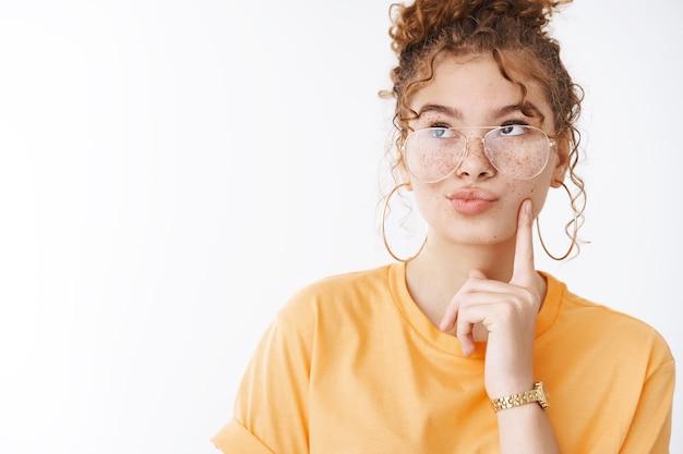 Elegante glamour atrevido jovem ruiva feminina usando óculos camiseta laranja dobrando lábios fazendo beicinho olhar pensativo canto superior esquerdo pensando lembrar número entrega serviço fazer escolha mente