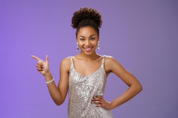 Elegante glamour confiante atraente mulher afro-americana em um vestido de noite prata brilhante apontando o dedo indicador esquerdo, sensualmente sorrindo, segurar a mão na cintura, apresentar o produto, posando com um fundo azul.
