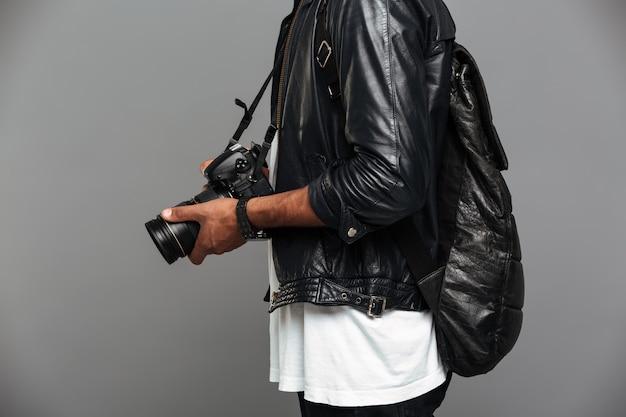 Elegante homem africano com mochila segurando a câmera fotográfica