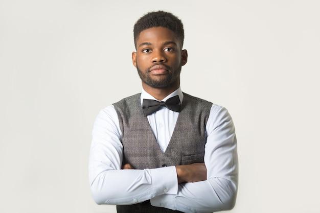 Elegante homem africano com um colete na parede branca