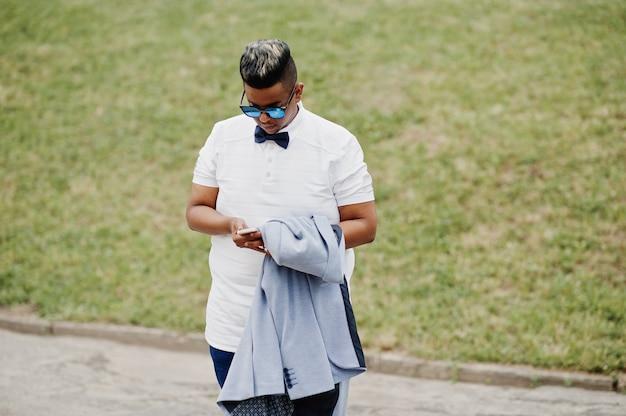 Elegante homem árabe com jaqueta, óculos escuros e gravata borboleta posou ao ar livre e olhando no celular. homem modelo árabe.