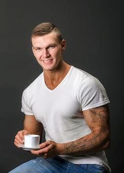 Elegante homem atlético sorrindo, segurando a xícara de café. sentado.