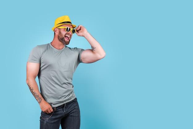 Elegante homem barbudo e musculoso e emocional com chapéu de palha amarelo, posando no estúdio sobre fundo azul