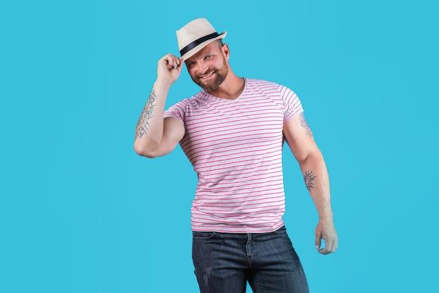 Elegante homem barbudo e musculoso sorridente com chapéu de palha, posando no estúdio sobre fundo azul