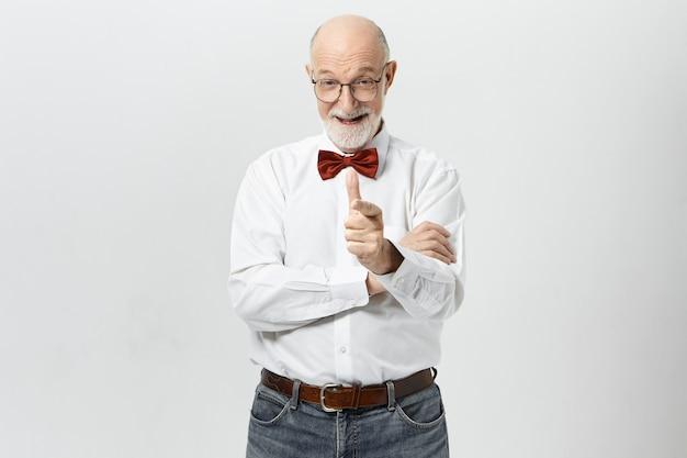 Elegante homem caucasiano sênior com barba espessa, expressando emoções positivas, apontando o dedo indicador e rindo. homem idoso com barba por fazer usando gravata borboleta e dizendo a você: bom trabalho