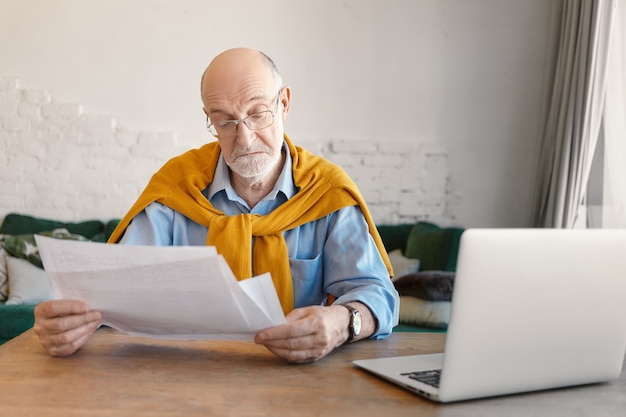Elegante homem idoso barbudo em óculos retangulares estudando folhas de papel nas mãos, calculando finanças domésticas online em casa, usando um dispositivo eletrônico portátil no interior da sala de estar