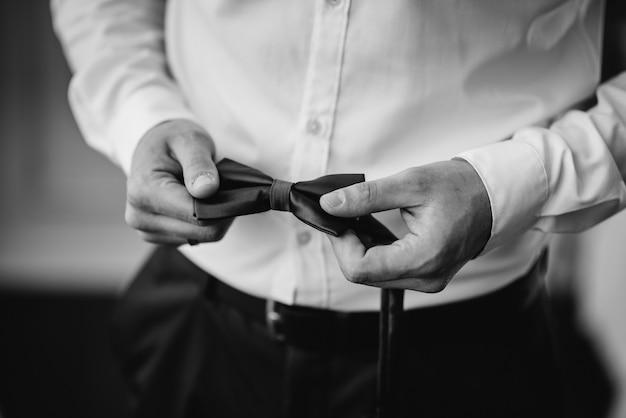 Elegante homem segurando uma gravata borboleta