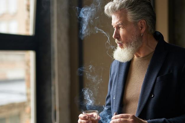 Elegante homem sério de meia-idade com barba olhando para longe enquanto segura um charuto e um copo de
