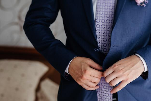 Elegante jovem abotoando os botões de punho nas mangas. estilo.