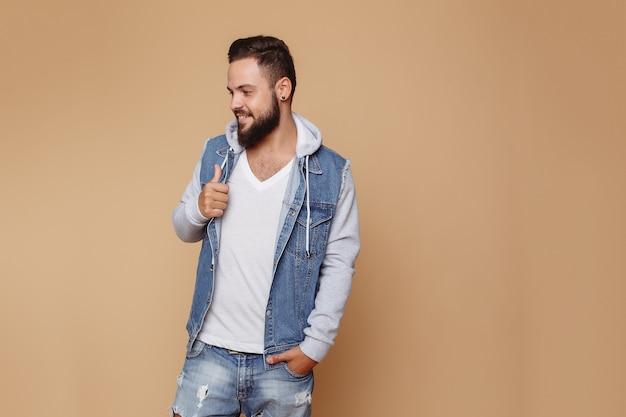 Elegante jovem alegre com uma bela barba em uma jaqueta jeans e camiseta branca em um espaço creme simples. conceito de publicidade de jaqueta jeans para outdoor.