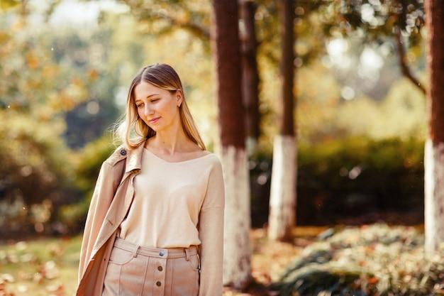 Elegante jovem andando no parque outonal