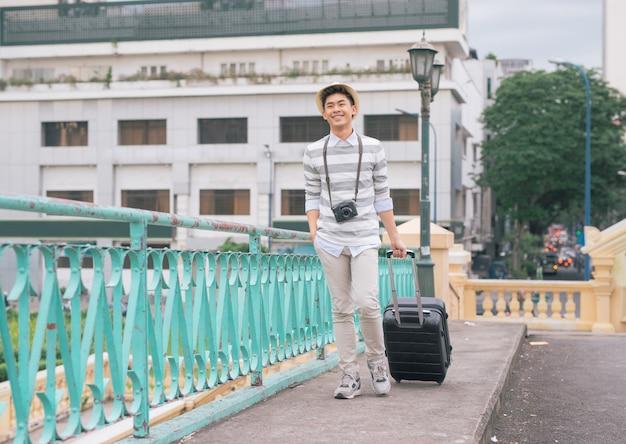 Elegante jovem asiático viajando com sua mala e segurando a câmera.