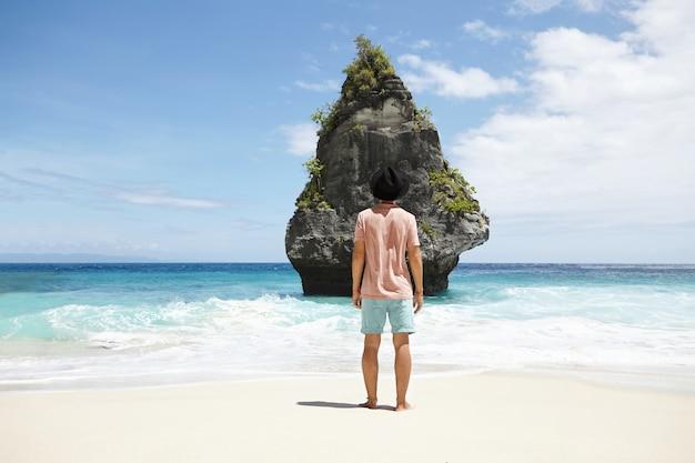 Elegante jovem aventureiro caucasiano com os pés descalços em frente a uma ilha de pedra deserta com vegetação que ele finalmente encontrou, contemplando a maravilhosa paisagem marinha, não consegue acreditar no que viu