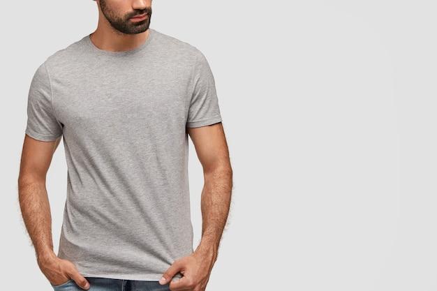 Elegante jovem barbudo em uma camiseta cinza grande demais e jeans, posa dentro de casa contra uma parede em branco