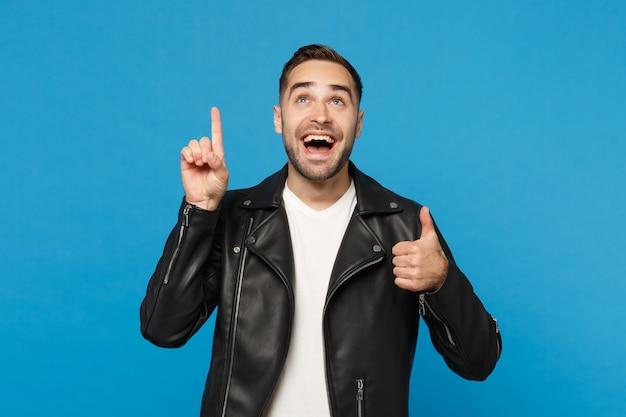 Elegante jovem barbudo na jaqueta de couro preta e camiseta branca, segurando o dedo indicador com uma ótima ideia isolada sobre fundo azul. conceito de estilo de vida de emoções sinceras de pessoas. simule o espaço da cópia.