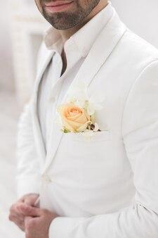 Elegante jovem bonito com barba em um terno branco clássico. o interior do hotel. estúdio fotográfico. sofá. janela. cadeira. lustre