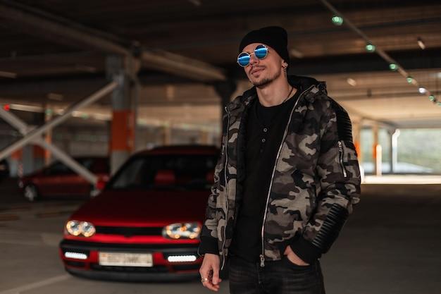 Elegante jovem bonito com óculos escuros e um chapéu com uma jaqueta militar de inverno da moda perto de um carro vermelho na cidade