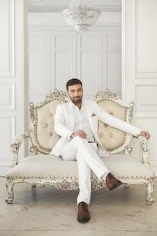 Elegante jovem bonito com uma barba em um terno branco clássico