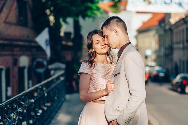 Elegante jovem casal apaixonado andando na rua ao pôr do sol
