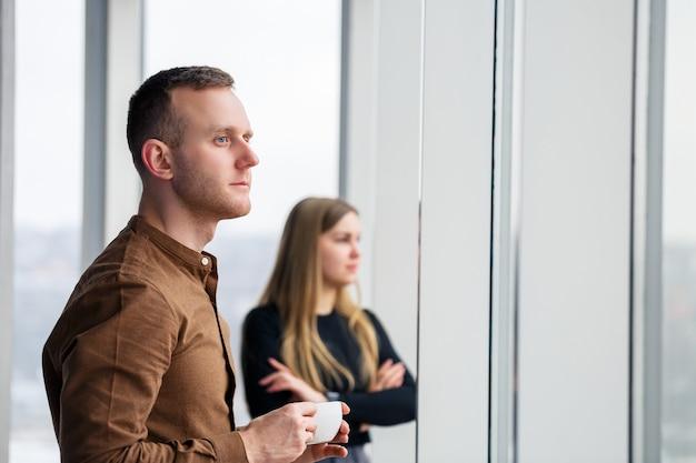 Elegante jovem casal apaixonado em frente a grandes janelas panorâmicas. uma jovem e um homem estão diante de uma grande janela com café. foco seletivo