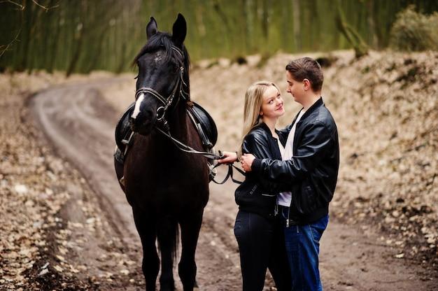 Elegante jovem casal apaixonado perto de cavalo na floresta de outono