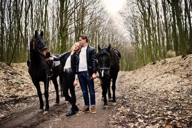 Elegante jovem casal apaixonado perto de cavalos na floresta de outono