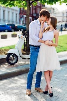 Elegante jovem casal apaixonado se abraçando, andando na velha cidade europeia