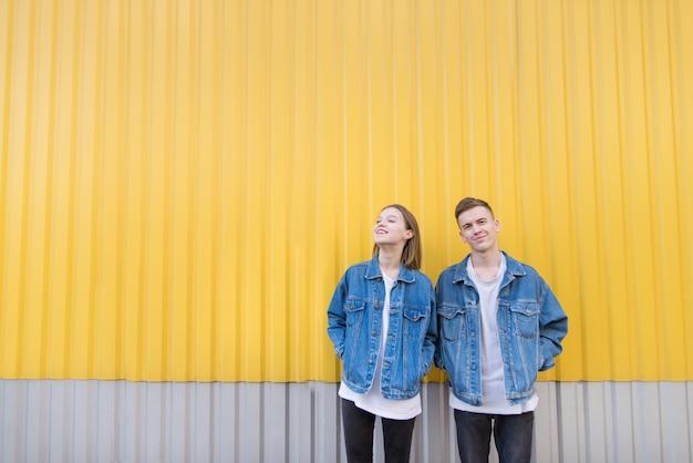 Elegante jovem casal dançando no fundo da parede amarela.