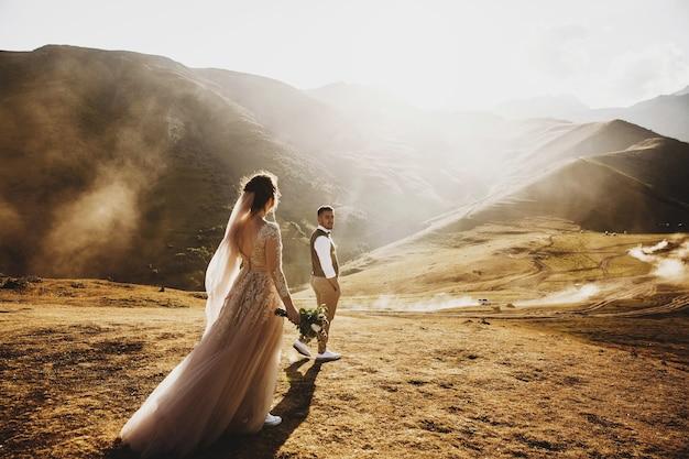 Elegante jovem casal de noivos se diverte posando em belas montanhas da geórgia