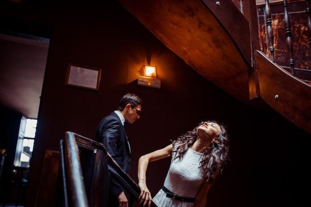 Elegante jovem casal em pé na escada e abraçando