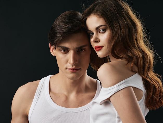 Elegante jovem casal homem e mulher, relações sexuais, dois modelos, fundo escuro