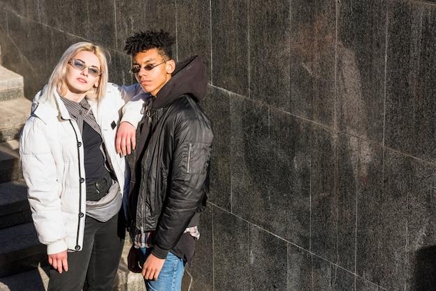 Elegante jovem casal usando óculos de sol em pé ao ar livre