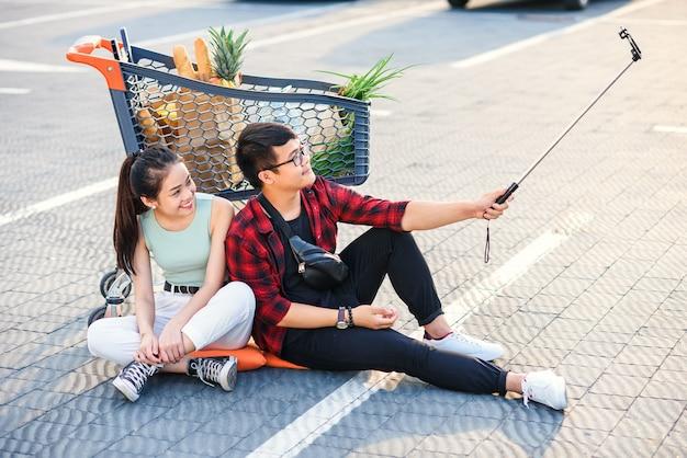 Elegante jovem casal vietnamita sentado no chão perto de carrinho de compras e fazendo selfie foto juntos.