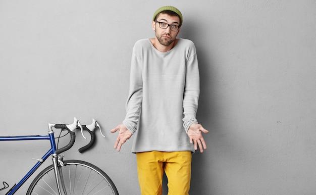 Elegante jovem ciclista em roupas da moda, com barba, encolher os ombros os ombros com incerteza, sem saber o que levar com ele em viagem, parado perto de sua bicicleta