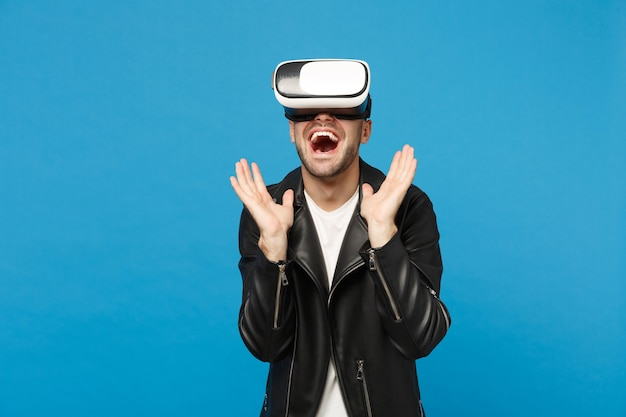 Elegante jovem com barba por fazer em t-shirt branca de jaqueta preta olhando no fone de ouvido, realidade virtual vr isolada no retrato de estúdio de fundo de parede azul. conceito de estilo de vida de emoções de pessoas. simule o espaço da cópia.