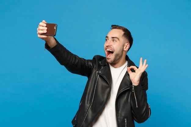 Elegante jovem com barba por fazer em uma jaqueta preta branca t-shirt oing selfie tiro no celular isolado no retrato de estúdio de fundo de parede azul. conceito de estilo de vida de emoções sinceras de pessoas mock up copy space