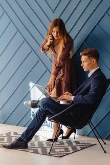 Elegante jovem com laptop e menina com telefone juntos, jovem empresário
