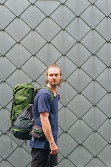Elegante jovem com mochila de viagem em pé contra a parede, olhando para longe