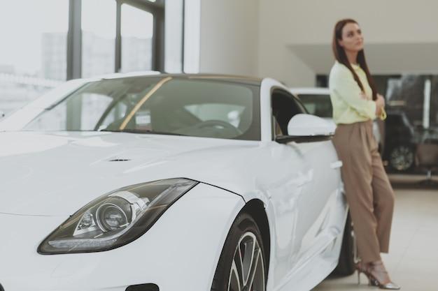 Elegante jovem comprando carro novo na concessionária