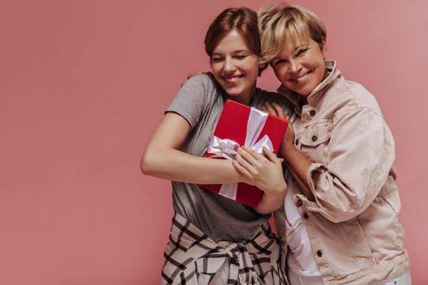 Elegante jovem de bom humor com morena cabelo curto, segurando uma caixa de presente, sorrindo e posando com uma mulher de cabelo loira no pano de fundo rosa.