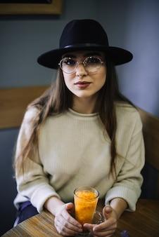 Elegante jovem de chapéu e óculos com copo de bebida