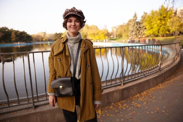 Elegante, jovem e bonita senhora de cabelos castanhos olhando positivamente com um sorriso gentil e mantendo as mãos para baixo enquanto está de pé sobre o parque desfocado em um dia quente de outono
