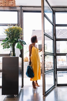 Elegante jovem em pé perto da entrada do restaurante