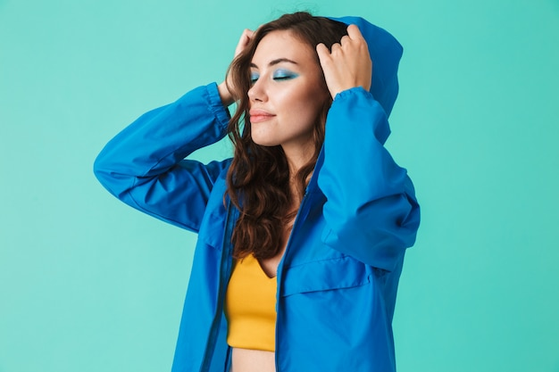 Elegante jovem em streetwear, colocando o capuz da capa de chuva ou jaqueta