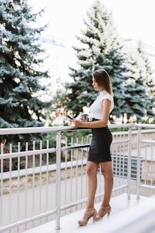 Elegante jovem empresária em pé na varanda olhando para celular
