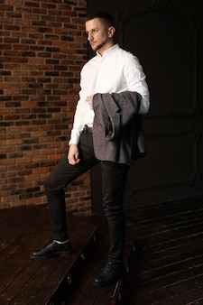 Elegante jovem empresário de camisa branca segurando uma jaqueta encostada na parede de tijolos